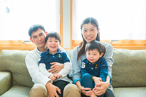 ソファーに座っている笑顔の4人家族