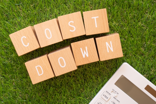 「COST DOWN」と書かれた積み木ブロックと電卓